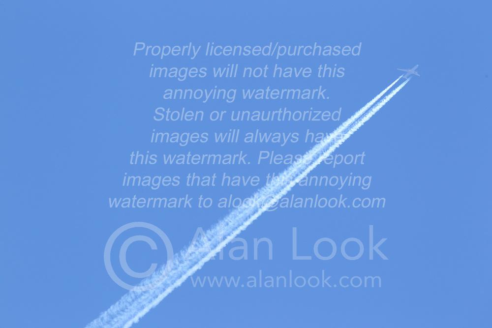 Passenger jet flies against the blue sky with a visible vapor trail
