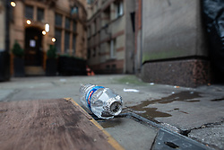 © Licensed to London News Pictures . 25/12/2018 . Manchester , UK . A discarded bottle with burned tin foil over the mouth , of a type commonly used as a makeshift drug pipe , on the street behind St Ann's Church in Manchester City Centre on Christmas Day . Photo credit : Joel Goodman/LNP