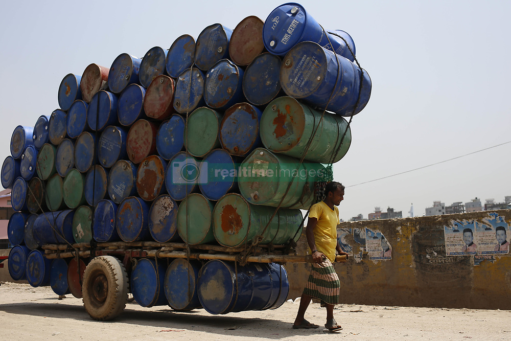 April 25, 2018 - Dhaka, Bangladesh - A man balances a wheelbarrow while delivering chemical drums for resale to a warehouse in Dhaka. (Credit Image: © Md. Mehedi Hasan via ZUMA Wire)