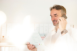 Male doctor reading a medical record and talking on a mobile phone, Munich, Bavaria, Germany