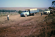 Unmade muddy and rutted highway road between Curitiba and Laranjeiras do Sol,, Paraná state, Brazil in 1962. A heavy goods vehicle carrying timber products and a bulldozer possibly for road construction in the background.