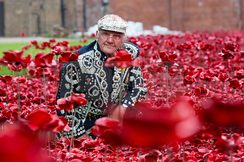 © Licensed to London News Pictures. 19/09/2014. London, UK. Pearly Kings and Queens plant ceramic poppies at The Tower of London's 'Blood Swept Lands and Seas of Red' ceramic poppy installation in central London on 19th September 2014 which commemorates the 100th anniversary of the outbreak of First World War. 'Blood Swept Lands and Seas of Red' is an evolving art installation and 888,246 poppies will be planted in the moat by volunteers, with the last poppy being planted on the 11th November 2014. Each poppy represents a British or Colonial fatality in the First World War. Photo credit : Vickie Flores/LNP