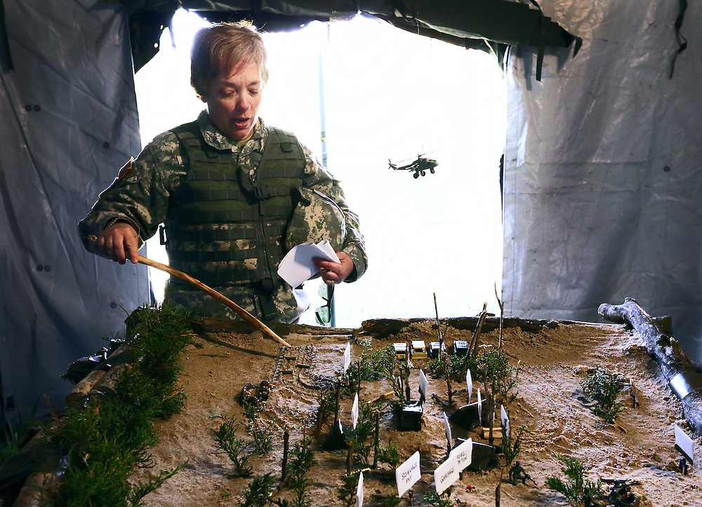 Sgt.1st Class Constance Oberg of the 443rd Transportation Company of the Army Reserve gives an overview of the field camp as a plastic helicopter provides close air support to the sand table model Saturday at Greenlief Training Site in Hastings. Soldiers set up the camp over five days to compete in the 43rd annual Philip A. Connelly Award food service competition. (Independent/Matt Dixon)