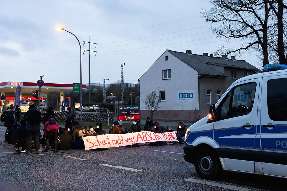 Mehrere hundert Menschen protestieren auf einer Kundgebung des Berliner Bündnisses gegen Abschiebungen am Flughafen Berlin-Brandenburg BER gegen eine geplante Sammelabschiebung nach Afghanistan. Neben der angemeldeten Kundgebung finden auch Aktionen des zivilen Ungehorsams statt. Aktivisten blockieren ein Gebäude des Abschiebegefängnisses auf dem Flughafengelände und die Mittelstraße. Vor dem Abflug laufen die Demonstranten direkt zum Zaun am Terminal 5, vor dem sie von der Polizei mit Pfefferspray gestoppt werden. Trotz Protesten und Blockadversuchen startet der Charterflug nach Kabul gegen 21:30 Uhr. Sitzblockade mit Banner: Schaut nicht weg! Abschiebung. Schönefeld, Deutschland, 07.04.2021.<br /> <br /> [© Christian Mang - Veroeffentlichung nur gg. Honorar (zzgl. MwSt.), Urhebervermerk und Beleg. Nur für redaktionelle Nutzung - Publication only with licence fee payment, copyright notice and voucher copy. For editorial use only - No model release. No property release. Kontakt: mail@christianmang.com.]
