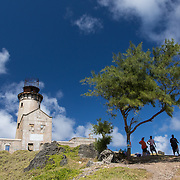 A group of people stand under a tree on Ile aux Fouquets, a small islet in the Blue Bay with a lighthouse. This island is sometimes visited by tourists during day trips.
