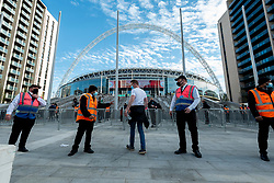 © Licensed to London News Pictures. 18/04/2021. LONDON, UK.  A spectator passes security guards outside Wembley Stadium ahead of the FA Cup semi-final match between Leicester City and Southampton.   4,000 local residents have been invited to attend the match, the largest number of spectators attending a match in a UK stadium for over a year.  Covid-19 testing will take before and after the match and data gathered will be used to plan how all sports tournaments can escape lockdown.  Photo credit: Stephen Chung/LNP