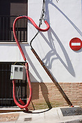 Artwork of electricity power cables and their shadows on a house wall.