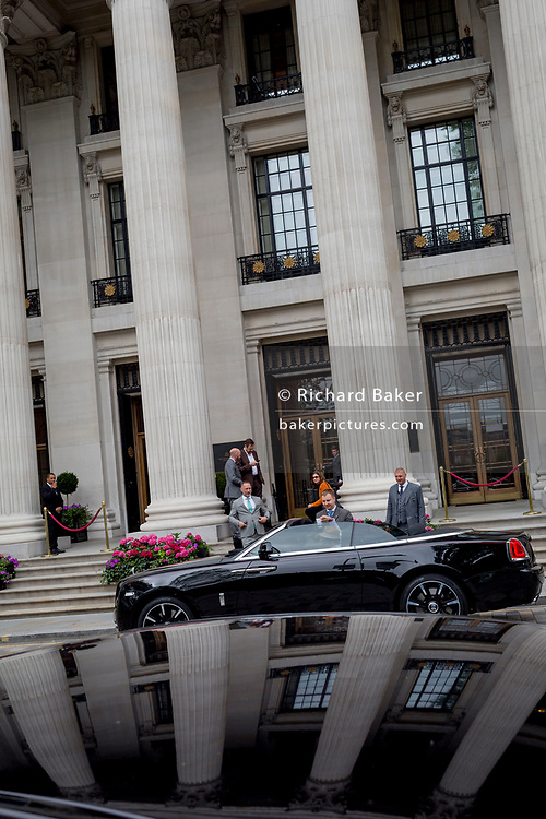 A polished black Bentley car parked outside the tall columns of the Four Seasons hotel at 10 Trinity Square in the City of London - the capital's financial district, on 4th June 2018, in London, England.