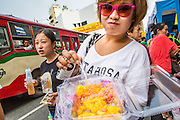 14 OCTOBER 2012 - BANGKOK, THAILAND:  A Thai woman shows off her vegetarian street food on the first day of the Vegetarian Festival in Bangkok's Chinatown. The Vegetarian Festival is celebrated throughout Thailand. It is the Thai version of the The Nine Emperor Gods Festival, a nine-day Taoist celebration beginning on the eve of 9th lunar month of the Chinese calendar. During a period of nine days, those who are participating in the festival dress all in white and abstain from eating meat, poultry, seafood, and dairy products. Vendors and proprietors of restaurants indicate that vegetarian food is for sale by putting a yellow flag out with Thai characters for meatless written on it in red.    PHOTO BY JACK KURTZ