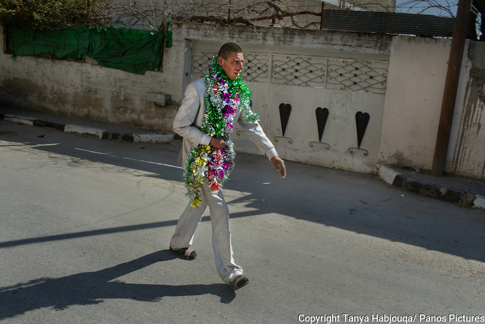 Man walks through West Bank village wrapped in celebratory tinsel. No one knew why .
