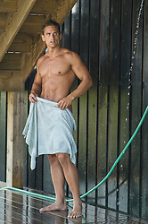 good looking man in an outdoor shower holding a towel