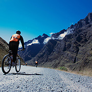 """Mountain Biking on Death Road, Bolivia...A tour group of Mountain Bikers make their way along tarmac road past breathtaking scenery as they travel along the first part of their journey heading towards the notorious jungle strip of 'Death Road'...The North Yugas Road is a 64 Kilometer road leading from La Paz to Corioico. It is legendary for it's extreme danger and in 1995 the Inter American Development Bank christened is as the """"world's most dangerous road"""".. The road was built in the 1930's during the Chaco War by Paraguayan prisoners to connect the Amazon rainforest region of Northern Bolivia to it's capital City La Paz. One estimate is that 200 to 300 travelers were killed yearly along the road. On 24 July 1983, a bus veered off the Yungas Road and into a canyon, killing more than 100 passengers in what is said to be Bolivia's worst road accident..A new stretch of the La Paz-Coroico highroad was opened in 2006 to bypass the notorious stretch known as death road..The danger of the road has now made it a popular tourist destination starting in the 1990's and drawing thrill-seekers and mountain bike enthusiasts who ride on the 64km mainly downhill stretch from La Cumbre, a 4,700 meter peak to Yolosa, a decent of 3600 meter's (11,800 feet). The journey includes breathtaking views of snow covered peaks and towering cliffs and starts along modern asphalted road before entering the jungle itself and the most dangerous and notorious part of the ride. The infamous narrow dirt road, most of the road no wider than 3.2meter's, is cut into the side of the mountain with sheer drops to the left of up to 600 meter's with virtually no safety rails on the winding steep decent..There are now many tour operators catering to this activity, providing information, guides, transport and equipment. Nevertheless, the Yungas Road remains dangerous. At least 13 of these cyclists died on the ride since 1998, the latest A 28-year-old Israeli traveler was killed in April 2010  the group of cy"""