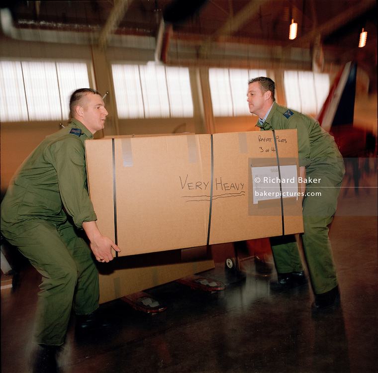 Corporal Andrew Haynes and Senior Aircraftman Michael Owen load boxes packed with the possessions and kit belonging to the elite 'Red Arrows' pilots, Britain's prestigious Royal Air Force aerobatic team, before travelling for winter training at Akrotiri in Cyprus. In the team's hangar at RAF Scampton, Lincolnshire, the two Suppliers lift the reinforced cardboard 'tri-pack' struggling to lift the weight from the ground. Corporal Haynes lifts with the correct technique: knees bent, straight back. The man on the right, has a bent back risking spinal injury. Some 80-plus members of the team will spend six weeks away from home. 23 tons of spares and personal effects travel ahead by ship with another 10 tons travelling on-board a C-130 transport aircraft. The Suppliers ensure possessions and spares are stored taking many weeks of meticulous planning. .