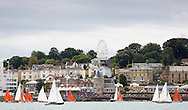The Squibs (red sails) and Victory class yachts pass the Royal Yacht Squadron during Aberdeen Asset Management Cowes Week. <br /> Picture date Tuesday 5th August, 2014.<br /> Picture by Christopher Ison. Contact +447544 044177 chris@christopherison.com