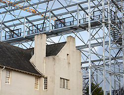 "Hill House in Helensburgh during construction of  ""box"" project to assist drying of the building exterior. Consists of a protective steel frame structure covered in chainmail mesh, featuring walkways around and over the top of the house. Scotland, UK."
