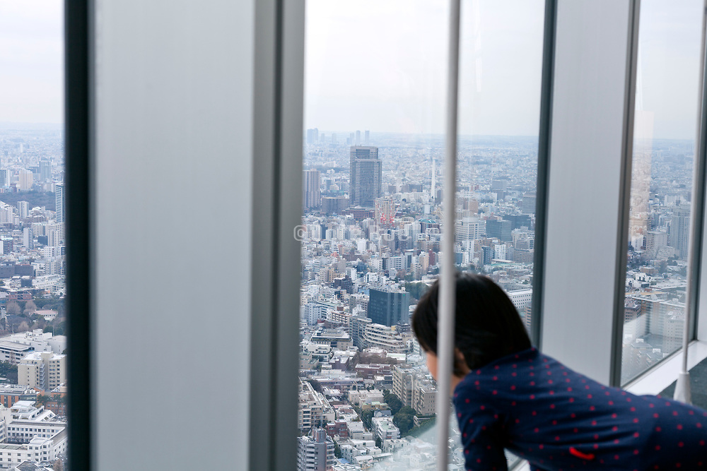 child looking out over the Tokyo aerial cityscape from the Miro Tower observation in Roppongi Hills