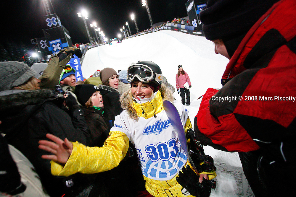 SHOT 1/25/08 8:17:38 PM - Snowboarder Gretchen Bleiler of Aspen, Co. high fives fans after winning gold in the Snowboard Superpipe Finals Friday January 25, 2008 at Winter X Games Twelve in Aspen, Co. at Buttermilk Mountain. Bleiler, a hometown favorite, won the event with a score of 93.33. The 12th annual winter action sports competition features athletes from across the globe competing for medals and prize money is skiing, snowboarding and snowmobile. Numerous events were broadcast live and seen in more than 120 countries. The event will remain in Aspen, Co. through 2010. Gretchen aspired to compete in the Olympic Games from a very young age, and found her passion in snowboarding at age 11 (1992). She has been riding ever since, became professional in 1996 and is currently recognized as a role model and pioneer in the sport. Among her accomplishments, Gretchen jump-started the invert revolution for female riders as the first to land a Crippler 540 in competition, and won more halfpipe competitions in 2003, 2005 and 2006 than any other female snowboarder. In the pre Olympic season she won four of the five US Olympic halfpipe qualifiers and is also a three time X Games gold medalist, most recently winning the superpipe at Winter X Games XII..(Photo by Marc Piscotty / © 2008)