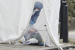 © Licensed to London News Pictures. 21/02/2018. London, UK. A Police forensics officer collects blood strainer evidence inside a police tent on Bartholomew Road, Camden, where one of two stabbings took place yesterday evening, killing two young men. Police were called to a second disturbance in the area, in which a second man was stabbed to death, and are currently investigating if the two incidents are connected. Photo credit: Peter Macdiarmid/LNP