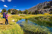 Backpacker and tarn on the Bishop Pass Trail, John Muir Wilderness, Sierra Nevada Mountains, California USA