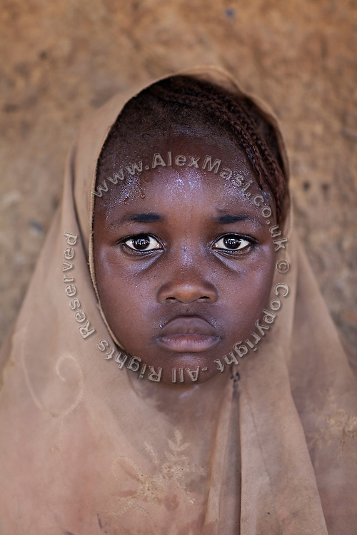 A girl is standing inside the affected village of Bagega, pop. 9000, Zamfara State, Nigeria, next to a large artisanal gold processing site. The lead contamination in the area is caused by ingestion and breathing of lead particles, released in the steps to isolate the gold from other metals. This type of lead is soluble in stomach acid and children under-5 are most affected, as they tend to ingest more through their hands by touching the ground, and are developing symptoms often leading to death or serious disabilities.