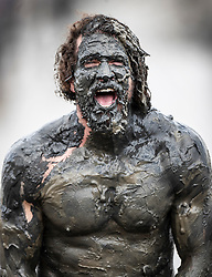 © Licensed to London News Pictures. 12/05/2019. Maldon, UK. A competitor celebrates finishing the Maldon Mud Race in Essex. The race originated in 1973 and involves competitors racing around a course on the mudbanks of the river Blackwater at low tide. Photo credit: Peter Macdiarmid/LNP