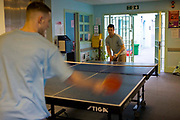 Two prisoners at YOI Aylesbury play table tennis during association time on H wing. Buckinghamshire, United Kingdom. Under the Incentives and Earned Privilege Scheme, prisoners in the UK can earn extra privileges for good behaviour such as wearing their own clothes, having televisions in their cells, and having more free time to socialise. They are often housed together in their own wing. There are three levels of earned privileges - Basic, Standard and Enhanced. HMYOI / HM Prison Aylesbury (Her Majesty's Young Offender Institution Aylesbury) is a prison is operated by Her Majesty's Prison Service.
