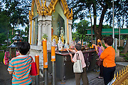 07 JULY 2011 - BANGKOK, THAILAND:   People pray at a Buddhist shrine in Lumpini Park. Lumphini Park (also Lumpini or Lumpinee) is a 360-rai (57.6-hectare or 142-acre) park in Bangkok, Thailand. The park offers open public space, trees and playgrounds in the Thai capital and contains an artificial lake where visitors can rent a variety of boats. Paths around the park totalling approximately 2.5 km in length are a popular area for evening joggers. Lumpini Park was created in the 1920s by King Rama VI on royal property. A statue of the king stands at the southwestern entrance to the park. It was named for Lumbini, the birthplace of the Buddha in Nepal, and at the time of its creation stood on the outskirts of the city. Today it lies in the heart of the main business district and is in the Lumphini sub-district, on the north side of Rama IV Road, between Ratchadamri Road and Witthayu (Wireless) Road.      PHOTO BY JACK KURTZ