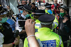 London, UK. 11th May, 2021. Metropolitan Police officers search an activist across the street from a protest by Palestine Action outside the UK headquarters of Elbit Systems, an Israel-based company developing technologies used for military applications including drones, precision guidance, surveillance and intruder-detection systems. The activists were protesting against the company's presence in the UK and in solidarity with the Palestinian people following attempts at forced evictions of Palestinian families in the Sheikh Jarrah neighbourhood of East Jerusalem, the deployment of Israeli forces against worshippers at the Al-Aqsa mosque during Ramadan and air strikes on Gaza which have killed several children.