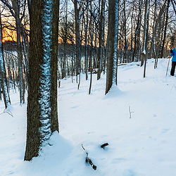 A woman snowshoeing during a winter sunset at the Indian Hill Preserve in West Newbury, Massachusetts.