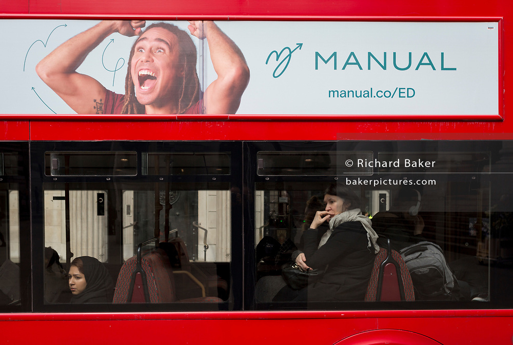 Serious bus passengers and an ecstatic man advertising  Manual, a product that helps with erectile dysfunction, on 25th March 2019, in London, England.
