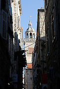 Belltower and cupola of Saint Mark's (Sveti Marko) Cathedral viewed through narrow streets. Korcula old town, island of Korcula, Croatia.