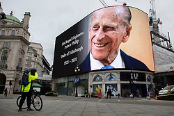© Licensed to London News Pictures.10/04/2021. London, UK. A member of the public takes a picture of a tribute to Prince Philip that is displayed on a large screen in Piccadilly Circus. Yesterday Buckingham Palace announced that Prince Philip The Duke of Edinburgh passed away in the morning at Windsor Castle . Photo credit: George Cracknell Wright/LNP