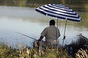 man sitting fishing at a lake