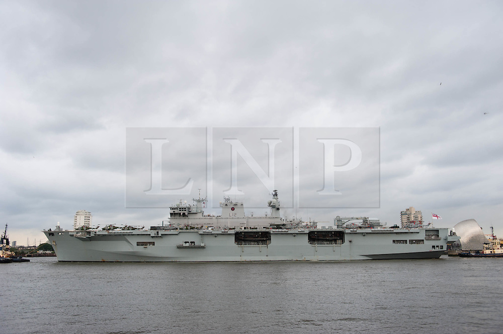 © Licensed to London News Pictures. 13/07/2012. Thames Barrier, London.  The Royal Navy helicopter carrier HMS Ocean passes through the River Thames Barrier.   It will be berthed at Greenwich throughout the Olympics, acting as logistic hub and helicopter launch platform.  The ship previously sailed up the Thames on May 4 as part of an Olympics security exercise.  Photo credit : Richard Isaac/LNP