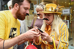 """© Licensed to London News Pictures. 05/09/2018. LONDON, UK.  Fans of Freddie Mercury and members of the public in Carnaby Street don moustaches during """"Freddie for a Day"""", a fundraising event in aid of the Mercury Phoenix Trust on Freddie Mercury's birthday.  Queen tribute band """"Bulsara and the Queenies"""" sang iconic songs entertaining crowds.  Photo credit: Stephen Chung/LNP"""