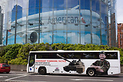 An army recruitment coach drives beneath a large advert for American Airlines of a wide-bodied airliner in Waterloo, south London. The words Leadership, Teamwork and Tactics are seen written on the side of the bus alongside the image of a tank and a professional soldier with arms folded. Helicopters fly in the vehicle's windows. Above is a large billboard advertising American Airlines, their wide-bodied airliner seemingly flying across the landscape.