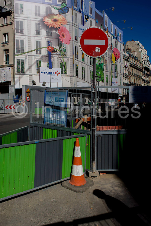 Street roadworks barriers and retail shop hoarding in Rue de Rivoli, Paris. With a prominent No Entry sign, a person's shadow and the green barriers in the foreground, we see in the distance large flowers adorning the side of a new store for the Spanish footwear company, Camper. Rue de Rivoli (French pronunciation: [ʁy də ʁivɔli]) is one of the most famous streets of Paris, a commercial street whose shops include the most fashionable names in the world. It bears the name of Napoleon's early victory against the Austrian army, at the battle of Rivoli, fought January 14 and 15, 1797. The rue de Rivoli marked a transitional compromise between an urbanism of prestige monuments and aristocratic squares, and the forms of modern town planning by official regulation.
