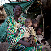 A Nuba family seats under the shade of a tree near their improvised home in the mountains outside Buram village in South Kordofan's Nuba Mountains.