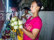 18 FEBRUARY 2015 - BANGKOK, THAILAND: A woman sells lotus buds in front of a Chinese shrine in the Kudeejeen neighborhood in Bangkok. PHOTO BY JACK KURTZ