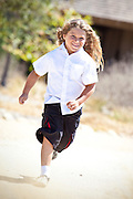 Young Boy With Long Blonde Wavy Hair Running At The Park