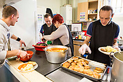 Staff and volunteers serving  food for the homeless . Slough Homeless our concern (SHOC) A local homeless charity helping the homeless and vulnerable in Slough. Berkshire, UK.
