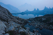 Whatcom Peak disappears from view as smoke from a nearby forest fire envelopes the beautiful alpine basin of Tapto Lakes, North Cascades National Park, Washington.