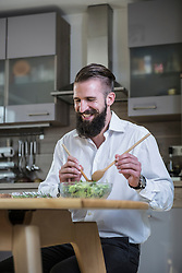 Man preparing salad in the kitchen and smiling, Bavaria, Germany