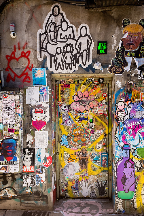 """Street art on and around a doorway, Freeman Alley, the Bowery, New York City. On the upper right is a figure of Donald Trump on which you can make out the word """"tyrant""""; on the the lower left is a blue-faced Donald Trump poster, labelled """"traitor."""""""