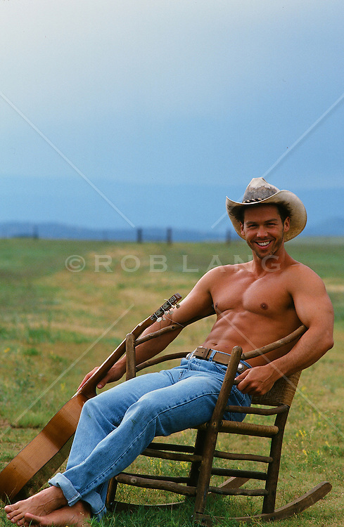 shirtless cowboy sitting in a rustic chair on a ranch