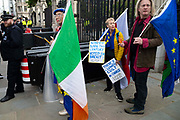 An anti brexit protester stands with an Irish flag outside the Houses of Parliament in London, United Kingdom on 3rd October 2019. Prime Minister Boris Johnson has published his  EU withdrawal agreement with a alternative to the Irish backstop telling EU leaders the UK will be leaving on 31 October with or without a deal.