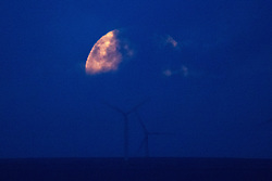 © Licensed to London News Pictures. 31/10/2020. Manchester, UK. A rare , Halloween Blue Moon is seen obscured by clouds , rising over Scout Moor Wind Farm , north of Manchester . Photo credit: Joel Goodman/LNP