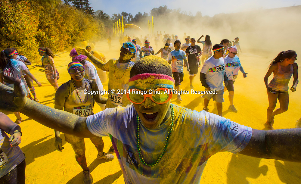 "6月21日,美國加利福尼亞州洛杉磯道奇球場外舉行""彩色跑""運動,超過萬名跑步愛好者參加。""彩色跑""是一項娛樂跑步項目,發源於美國,每年在北美,南美,歐洲,亞洲和澳大利亞同時舉行。項目全程為5公里,每公里設置一個彩色站,當參與者跑至彩色站時,由志願者向參與者拋灑彩色粉末。它融合了跑步和色彩,與傳統跑步競速相比,雖然它沒有贏家或獎品,但強調""參與、娛樂和色彩""的重要性。圖為跑步愛好者跑過彩色站。(新華社發 趙漢榮攝)<br /> Running enthusiasts race through clouds of colorful powder thrown by volunteers during the Color Run on the Dodgers Stadium, Saturday, June 21, 2014 in Los Angeles, California. The Color Run is an event series and five kilometres paint race that takes place in North America, South America, Europe, Asia, and Australia. The untimed event has no winners or prizes, but runners are showered with colored powder at stations along the run. (Xinhua/Zhao Hanrong)(Photo by Ringo Chiu/PHOTOFORMULA.com)"