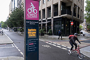A cyclist rides past annual cycling statistics for the North-South CS6 Superhighway that allows commuters safe journeys south of Blackfriars Bridge, on 21st June 2021, in London, England.