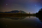 Hundreds of stars in the night sky shine over Mount Si and Borst Lake in this scene from Snoqualmie, Washington. Mount Si is a 4167 ft (1270 m) mountain that is located in neighboring North Bend. Mount Si is a remnant of an oceanic plate volcano. Its summit is a class 3 rock scramble known as the Haystack.